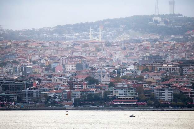 View of a district with residential and mosques in istanbul, bosphorus strait with moving boat on the foreground, turkey