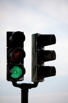 View of a double fork traffic light pole with a green light.