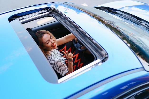 Vista di una donna alla guida attraverso il tetto apribile