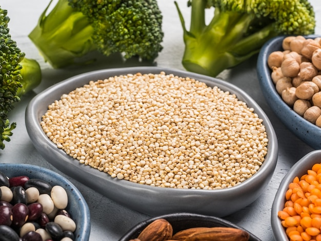 Above view of dry quinoa and other vagan protein sources on gray concrete background close up top view or flat lay copy space