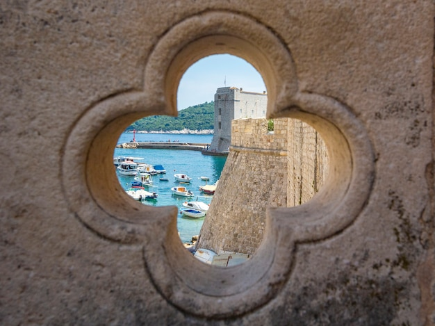 View of dubrovnik on old city, stone walls, sea and boats through lucky clover trefoil, dalamtia, croatia