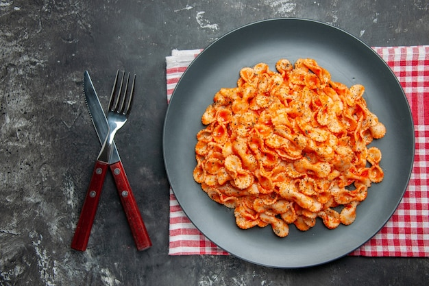 Above view of easy pasta meal for dinner on a black plate and cutlery set on a red stripped towel on a dark background