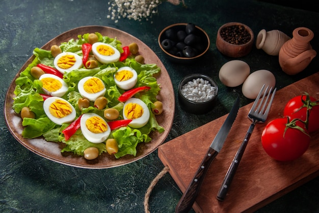 Above view egg salad consists of olives and green salad on dark blue background