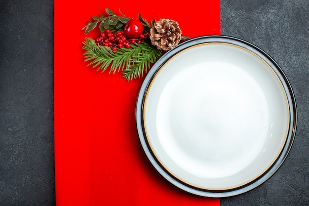 Above view of empty plates and fir branches with decoration accessory conifer cone on a red napkin on a dark background