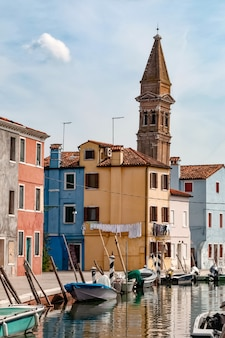 View on empty street with boats in water canal, typical colorful  houses and ancient tower in burano island, italy