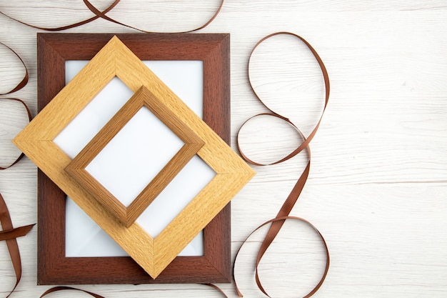 Above view of empty wooden picture frames in different sizes around ribbon on white