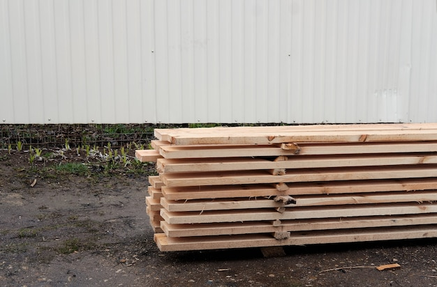 View of ends of stacked edged larch boards with beveled edge, planken for construction of fence or cladding house, timber prepaired for building