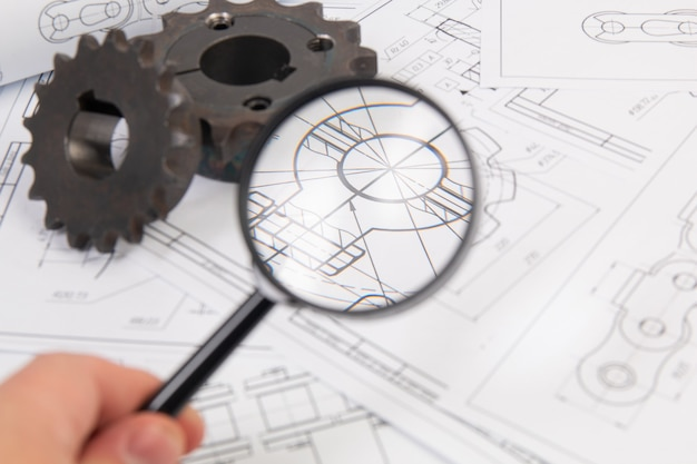 View of engineering drawings and sprocket for driving industrial roller chain through a magnifying glass