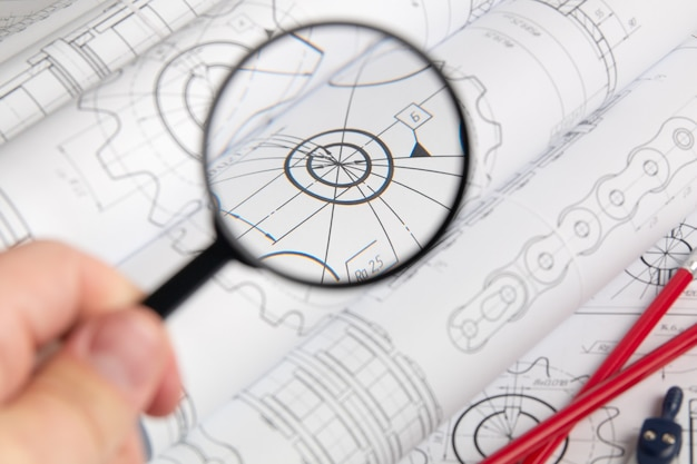 View of engineering drawings through a magnifying glass