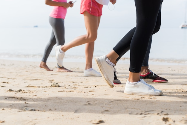 View of feet running on beach together