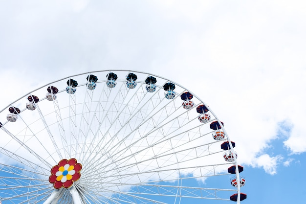 View of the ferris wheel against the background of blue sky and white clouds.