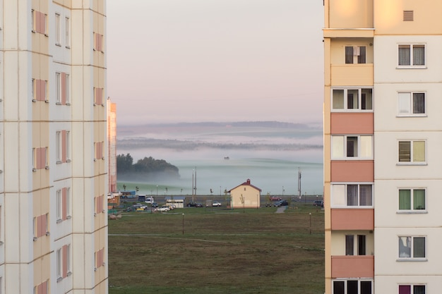 View of a field in the fog, bathed in morning light, between two multi-storey buildings in a residential area.