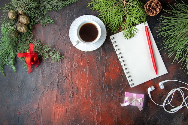 Sopra la vista dei rami di abete una tazza di accessori per la decorazione del tè nero cuffie bianche e regalo accanto al taccuino con penna su sfondo scuro