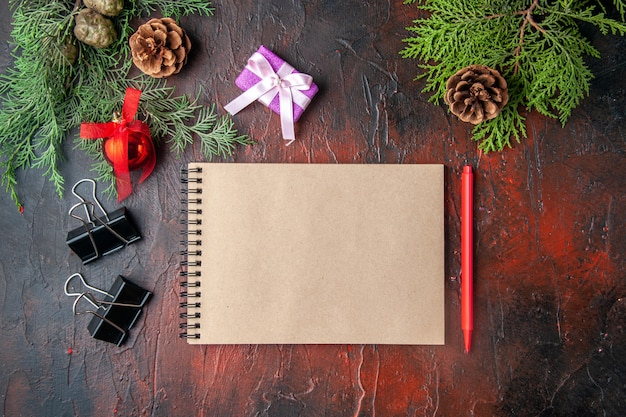 Above view of fir branches decoration accessories and gift next to notebook with pen on dark background