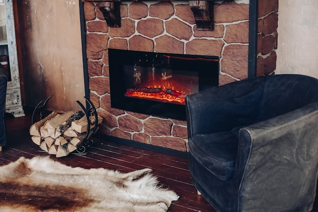 View over fireplace with burning logs, natural fur skin on the floor next to holder with logs in cozy room.