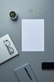 Above view flat lay of blank white paper on grey workplace background with smartphone and business accessories,