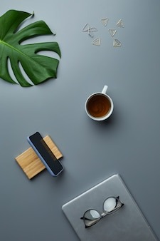 Above view flat lay of tropical leaf and business accessories over grey workplace background,