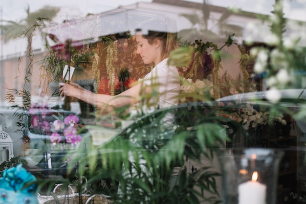 View of floral shop window with worker