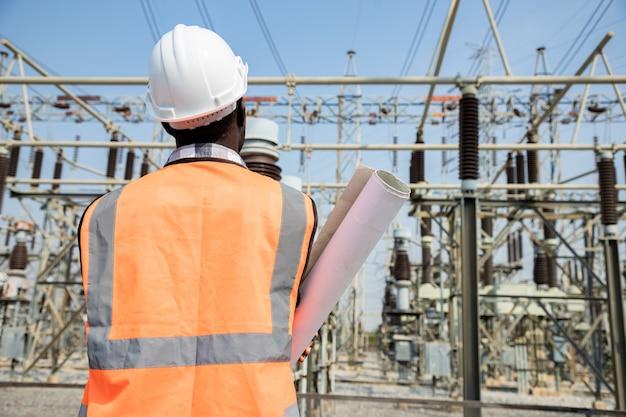 종이 프로젝트 계획을 들고 잘 생긴 엔지니어링 남자의 뒷면 양식을보고 고전력 발전소 앞에서 안전모를 착용하십시오. 발전소 건물의 배경에 계약자의 다시보기.