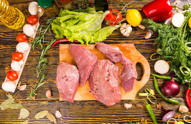 Above view on four cuts of raw red meat over wooden table surrounded by onions, tomatoes, mushrooms and other vegetables
