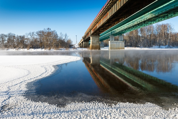 View on a freezing winter river bridge on the background