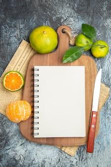 Vista dall'alto di agrumi freschi con foglie su tagliere di legno tagliato a metà e taccuino con coltello su giornale su sfondo grigio