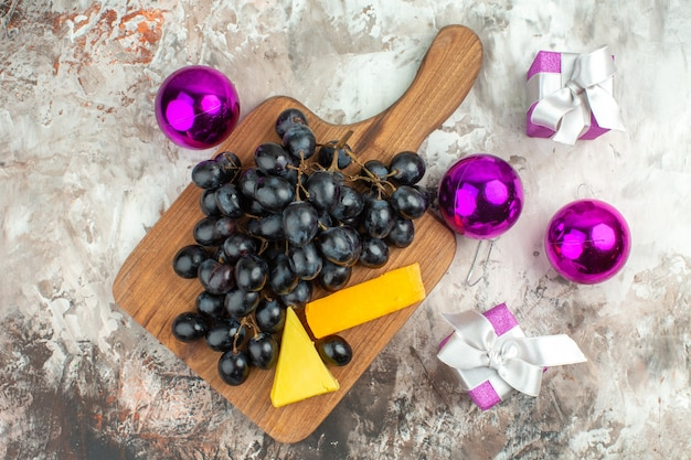 Above view of fresh delicious black grape bunch and cheese on wooden cutting board and gifts decoration accessories on mixed color background