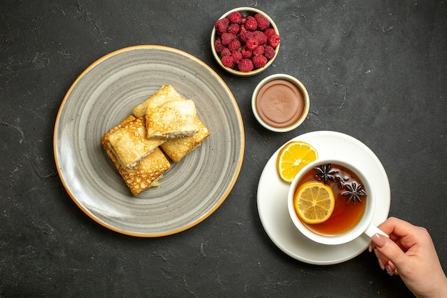 Above view of fresh delicious pancakes on a white plate and a cup of black tea chocolate raspberry decoration accessories on dark background
