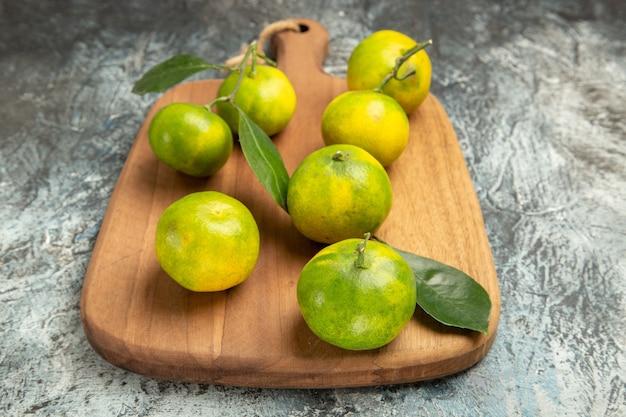 Sopra la vista di mandarini verdi freschi con foglie su tagliere di legno su sfondo grigio