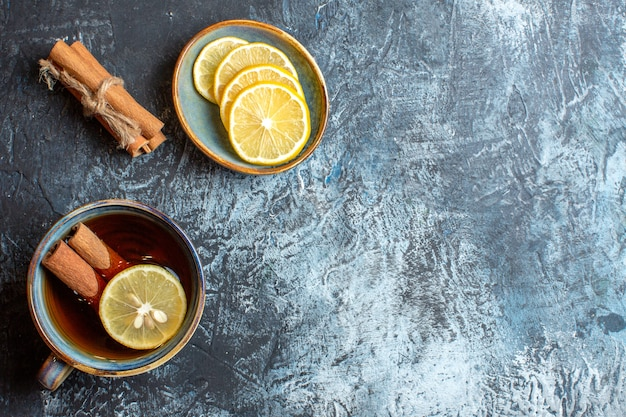 Above view of fresh lemons and a cup of black tea with cinnamon on the right side on dark background