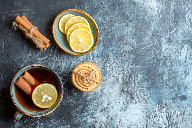 Above view of fresh lemons and a cup of black tea with cinnamon stacked cookies on the right side on dark background