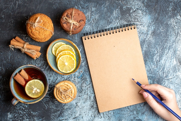 Above view of fresh lemons and a cup of black tea with cinnamon various stacked cookies and hand holding a pen onspiral notebook on dark background
