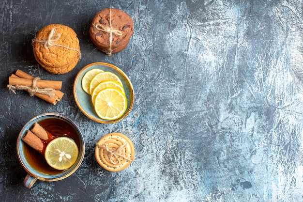 Above view of fresh lemons and a cup of black tea with cinnamon various tacked cookies on the right side on dark background