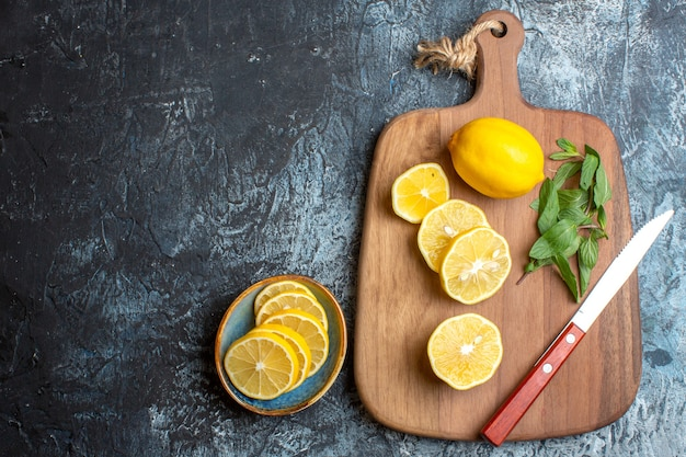 Above view of fresh lemons and mint knife on a wooden cutting board on the left side on dark background
