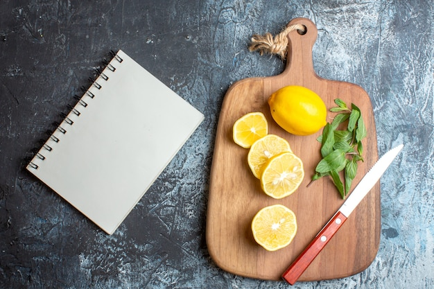 Above view of fresh lemons and mint knife on a wooden cutting board next to notebook on dark background