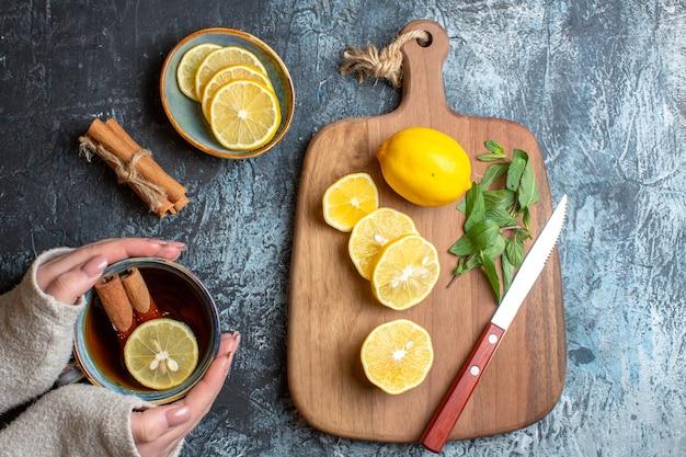 Sopra la vista di limoni freschi e coltello alla menta su un tagliere di legno