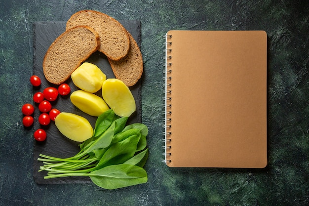 Above view of fresh peeled cut potatoes and dietary bread slices tomatoes green bundle on wooden cutting board spiral notebook on green black mix colors surface