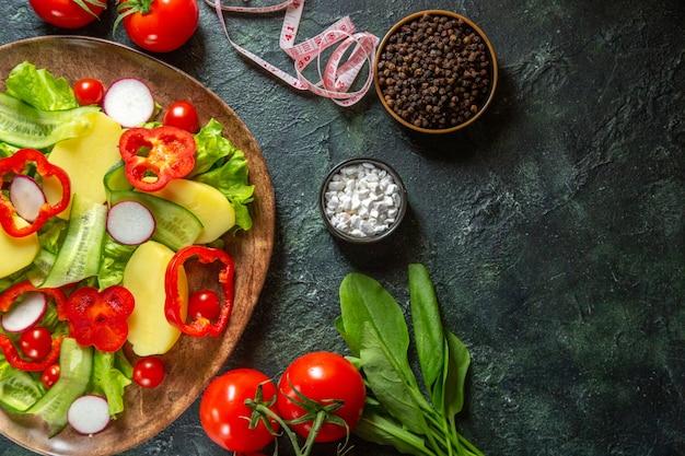 Sopra la vista di patate fresche sbucciate tagliate con peperoni rossi ravanelli pomodori verdi in una piastra marrone e metri di spezie su verde nero mescolare la superficie dei colori