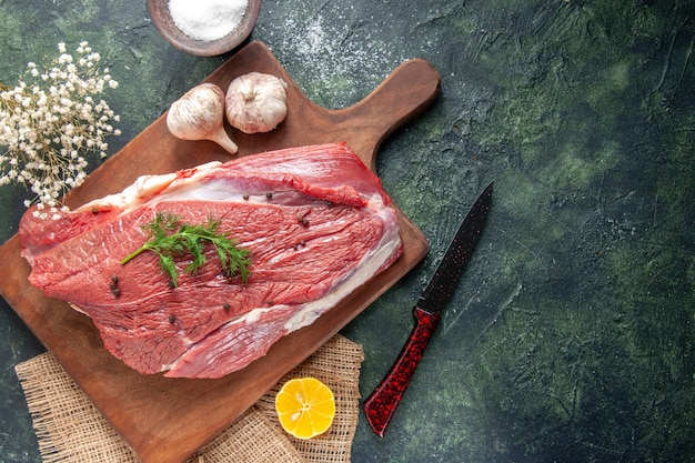 Sopra la vista di aglio crudo fresco di carne rossa su tagliere di legno limone su asciugamano di colore nudo farina di coltello fiore su sfondo di colore misto