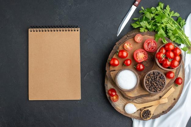 Sopra la vista di pomodori freschi e spezie in ciotole cucchiai su taccuino di legno su superficie nera