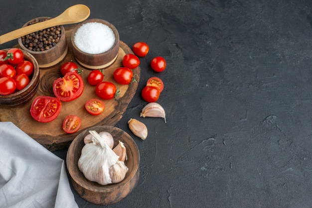Sopra la vista di pomodori freschi e spezie su tavola di legno asciugamani bianchi su superficie nera