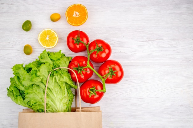 Sopra la vista di pomodori freschi con gambo e kumquat al limone verde sul lato destro su sfondo bianco