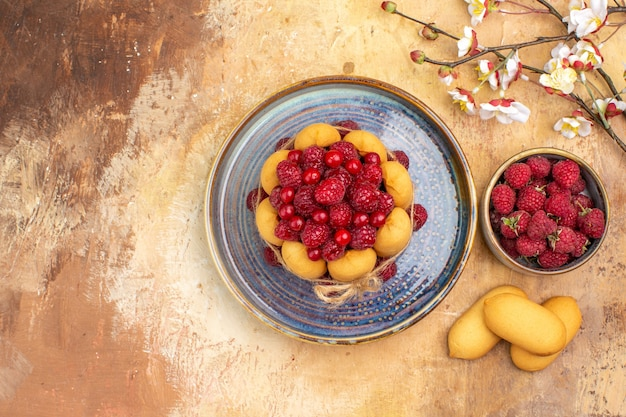 Above view of freshly baked soft cake with fruits and biscuits on mixed color table