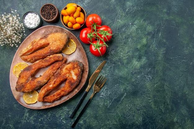 Sopra la vista di pesci fritti e fette di limone su un piatto marrone pomodori kumquat sul tavolo colori mix con spazio libero