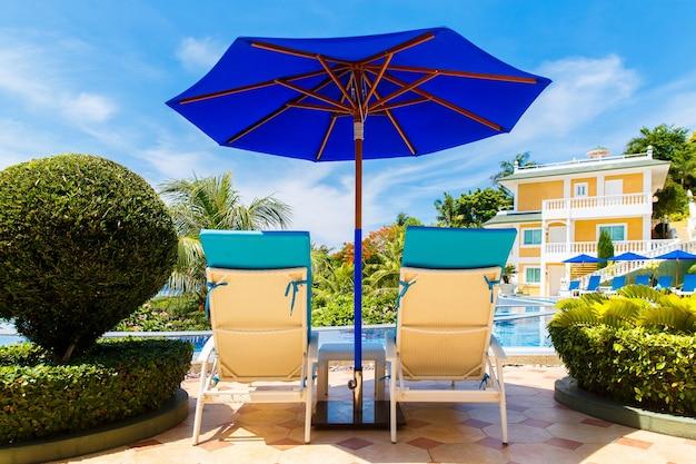 熱帯の島のインフィニティプールの前にあるサンラウンジャーとパラソルのあるホテルからの眺め