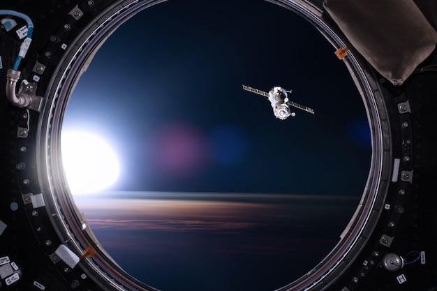 Вид из иллюминатора космической станции на фоне земли