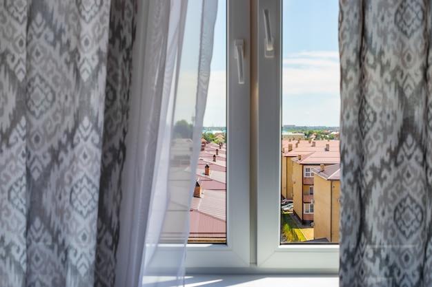 Вид из окна с приоткрытыми серыми шторами на дома и крыши зданий. интимные секреты жильцов, защита от посторонних глаз.