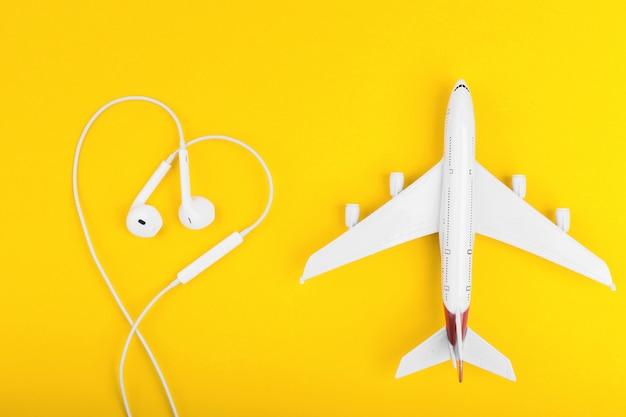Вид сверху на самолет и наушники в форме сердца на желтом столе.