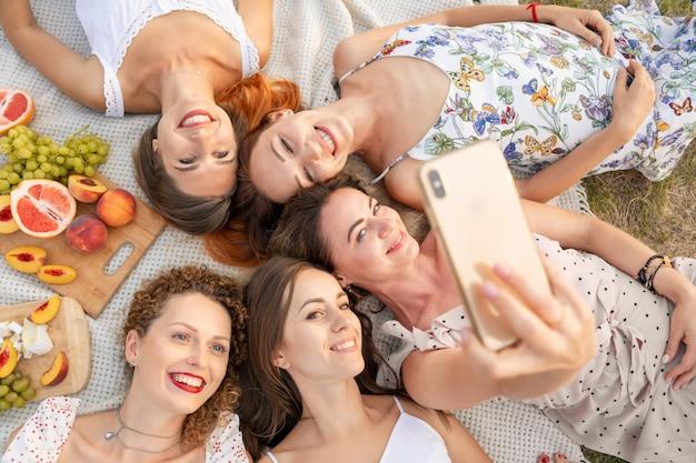 위에서 볼 수 있습니다. 아름다운 여자 친구가 재미 있고 야외 피크닉을 즐기고 휴대 전화로 사진을 찍습니다.