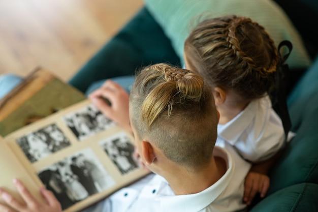 Вид сверху. дети мальчик и девочка сидят на зеленом диване и смотрят старый альбом с фотографиями
